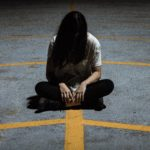 depressed woman with black hair sitting in middle of parking lot with head looking down