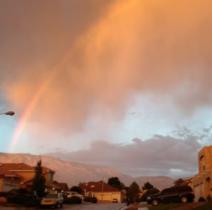 view-of-mountain-with-arching-rainbow-and-storm-clouds