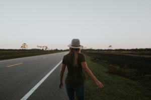 solo-woman-in-hat-walking-down-rural-road-early-morning